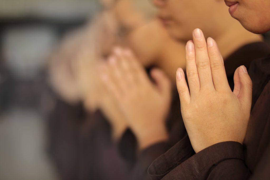Mehrere Personen heben ihre Hände zum Gebet.