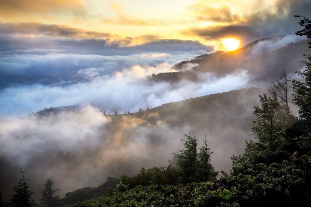 Sonne und Nebel liegen über einer Berglandschaft.