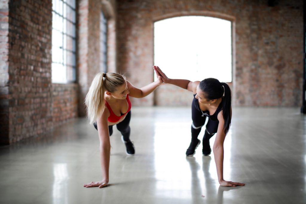 Zwei Frauen beim Sport geben sich ein High Five.