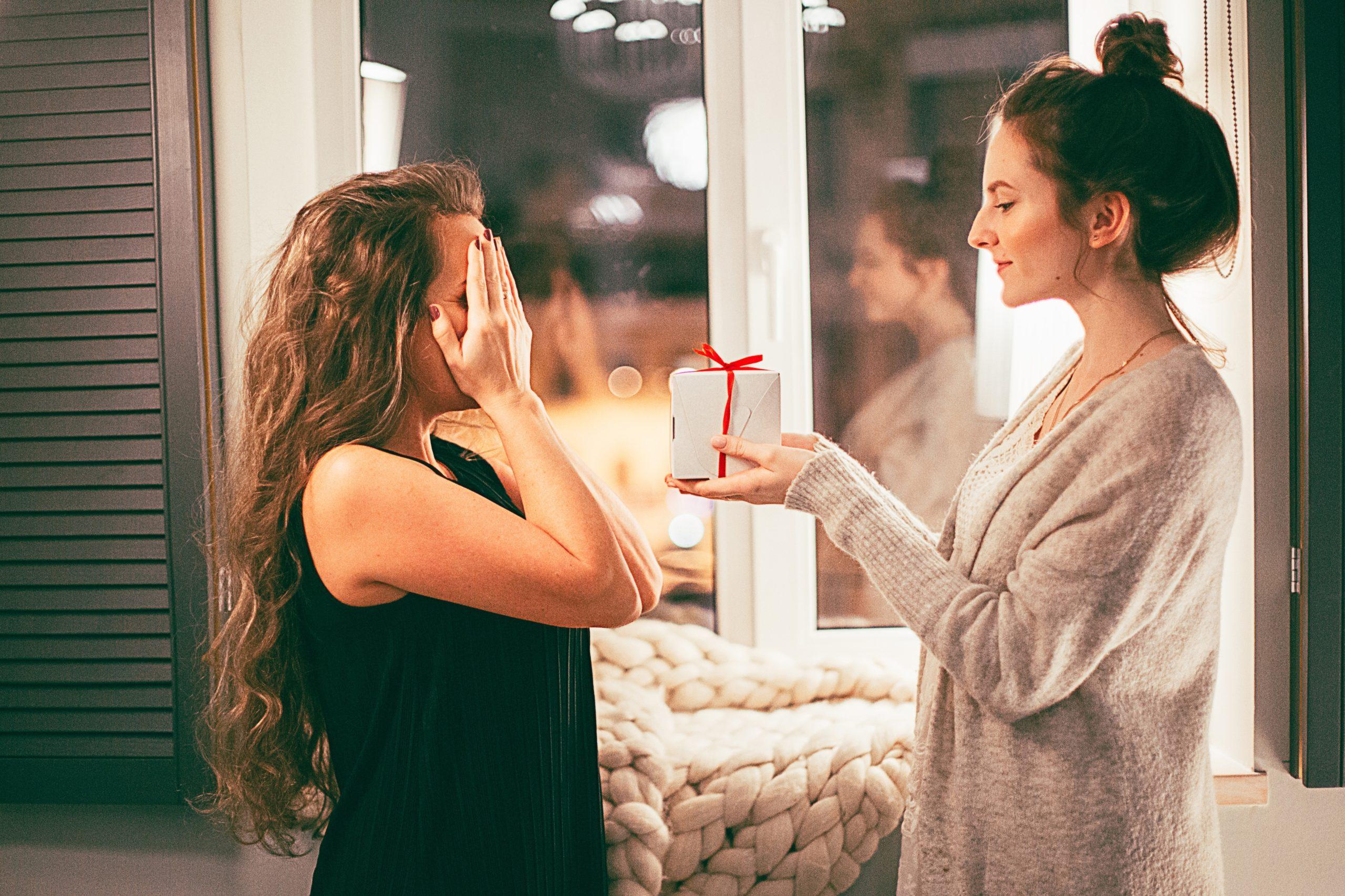 Eine Frau überreicht ihrer Freundin ein Geschenk.