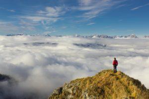 Ein Wanderer auf einem Fels über der dichten Wolkendecke.