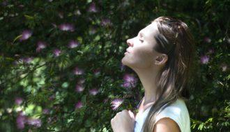 Junge Frau vor einer Wand aus Pflanzen und Blumen