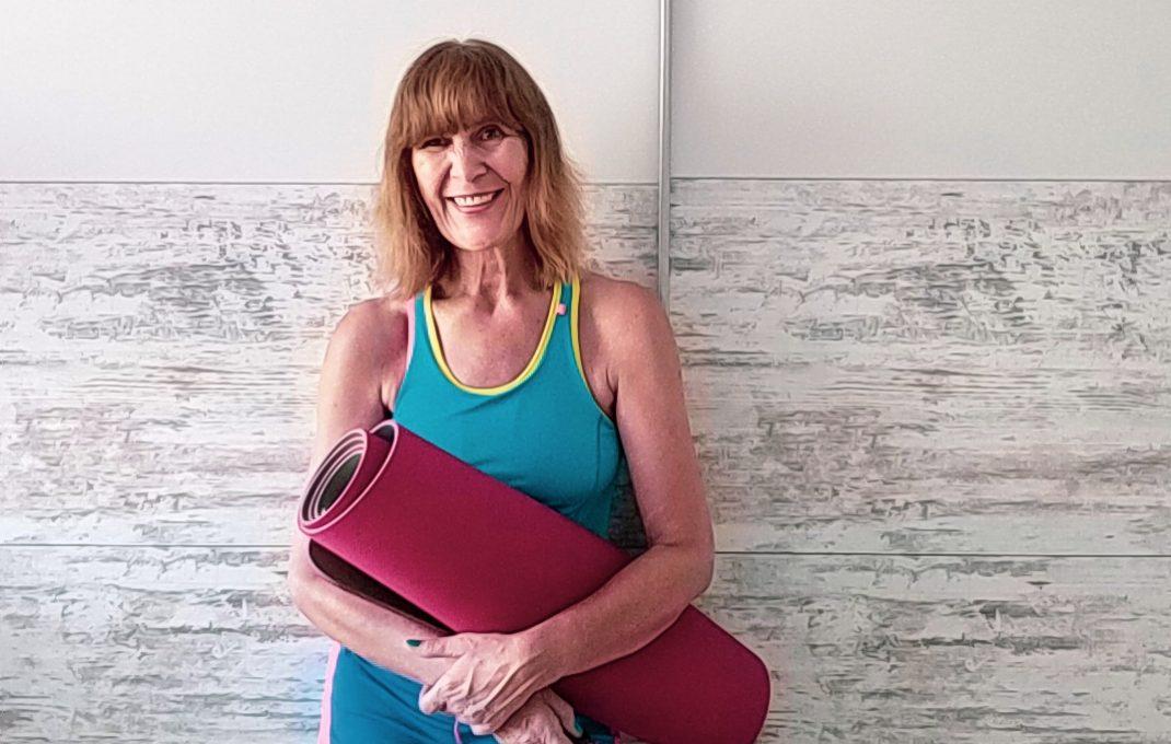 Eine Frau mit Sportmatte in Fitnesskleidung.